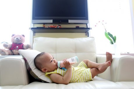 Baby on couch with bottle.