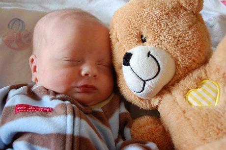 Sleeping infant with teddy bear.